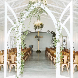 white arch backdrop with ivy with cross in the background