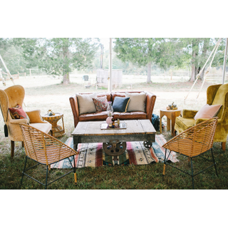 Vintage leather sofa with two vintage mustard chairs, two rattan chairs, and industrial cart table