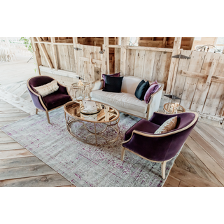 Linen sofa with two purple chairs, gold tables, and purple pillows