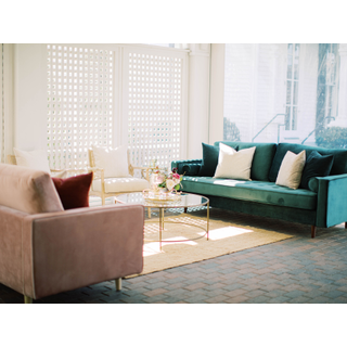 Pink couch, green couch, two linen chairs, gold coffee table, and jute rug