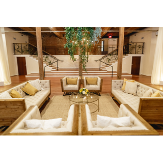 Two linen industrial sofas with four linen industrial chairs, gold round coffee table in middle