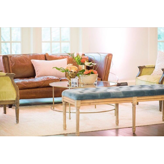 Leather sofa with colorful chairs and bench with gold coffee table