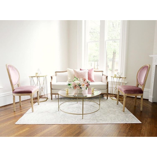Linen sofa with two pink chairs and gold coffee and side tables