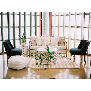 Linen sofa with two blue chairs, white side and coffee table, and white pouf