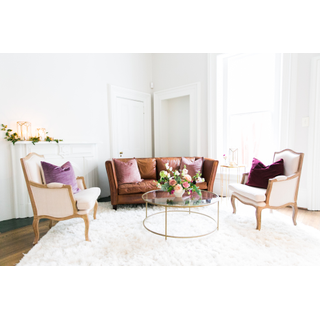 Leather sofa with two linen chairs on fluffy white carpet