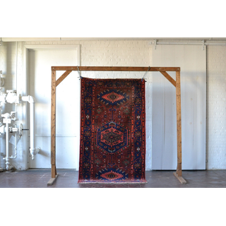 large jewel-toned red rug on white backround