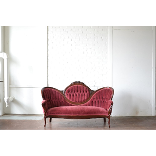 red burgundy cranberry colored vintage couch on white backround