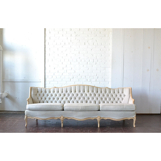 white neutral button tufted upholstered sofa