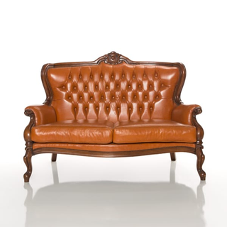 butterscotch leather settee with wood frame and nailhead trim