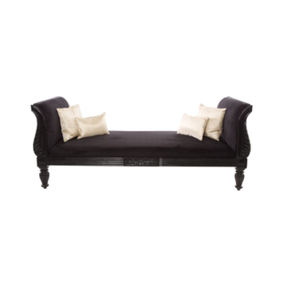 sleek black daybed with carved wood