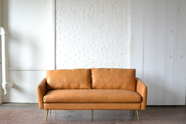 Tan leather mid centery sofa with gold legs