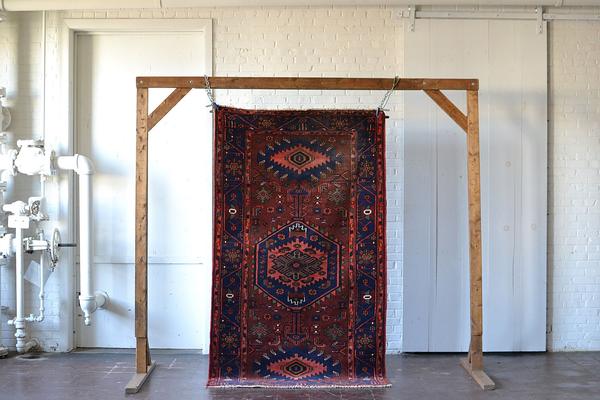 large jewel-toned red rug on white backround