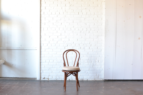 Vintage wooden Bentwood style chairs with neutral cushion on white background