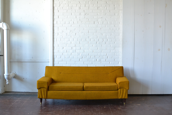 Mid-century yellow sofa with wooden legs and brass accents.