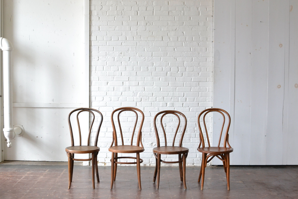 mismatched vintage wooden bentwood style chairs on white backround