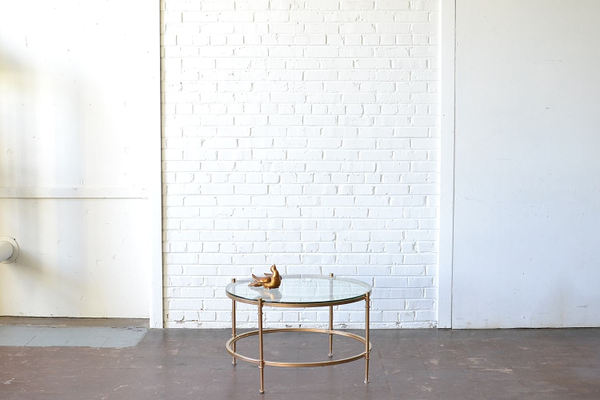 gold and glass coffee table on white backround