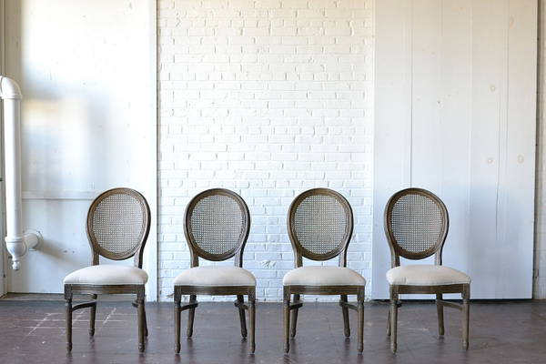 wooden neutral upholstered dining chair caned back on white background
