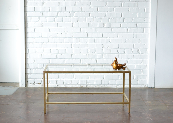 gold and glass coffee table on white brick background