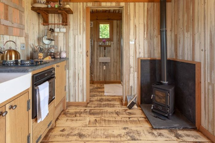 sit by the wood burner inside dunmore at huts in the hills in northumberland 1024 wide - Charming shepherd's hut boasts an ingenious bed with built-in dining table