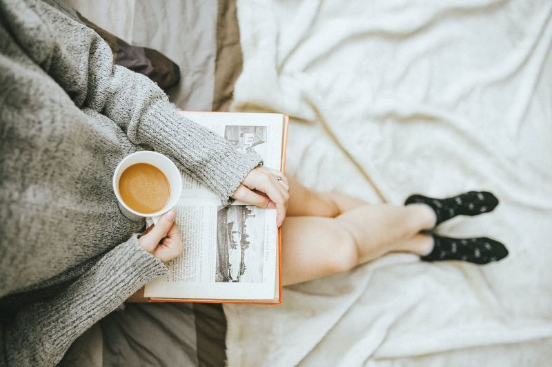 Woman relaxing with a book and coffee