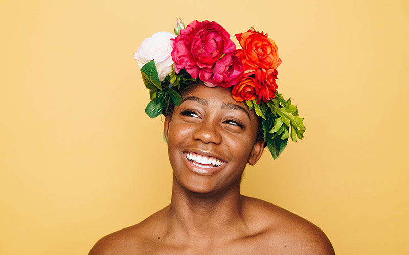 Woman on yellow backdrop with flower headdress