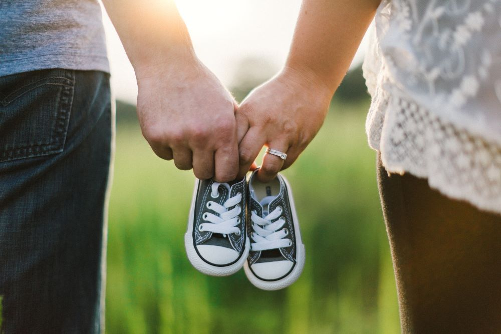 Couple expecting a baby holding baby shoes