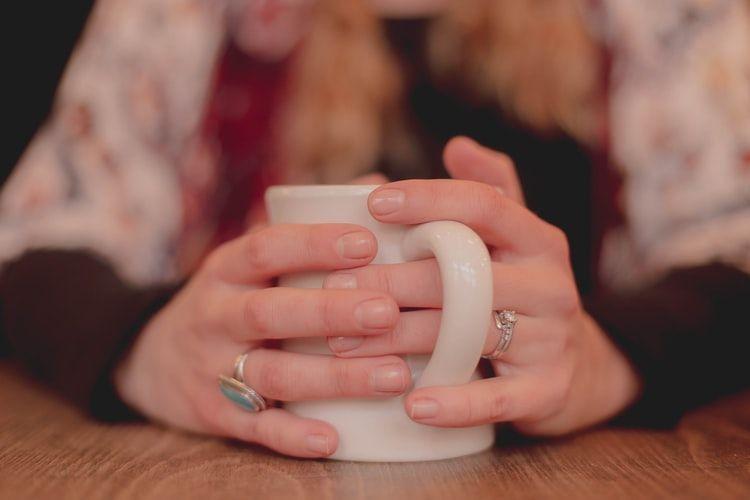 Woman warming hands on coffee