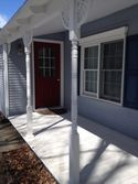 The Maples - A red front door welcomes guests from the front porch into the pleasing gray house with white trim!