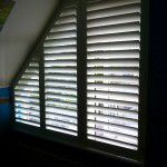 witte shutters schuin raam