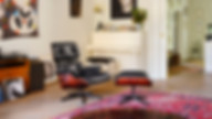 The Eames Lounge Chair and corresponding Ottoman in a cosy home setting with a pink-hued vintage rug, white piano and wall art
