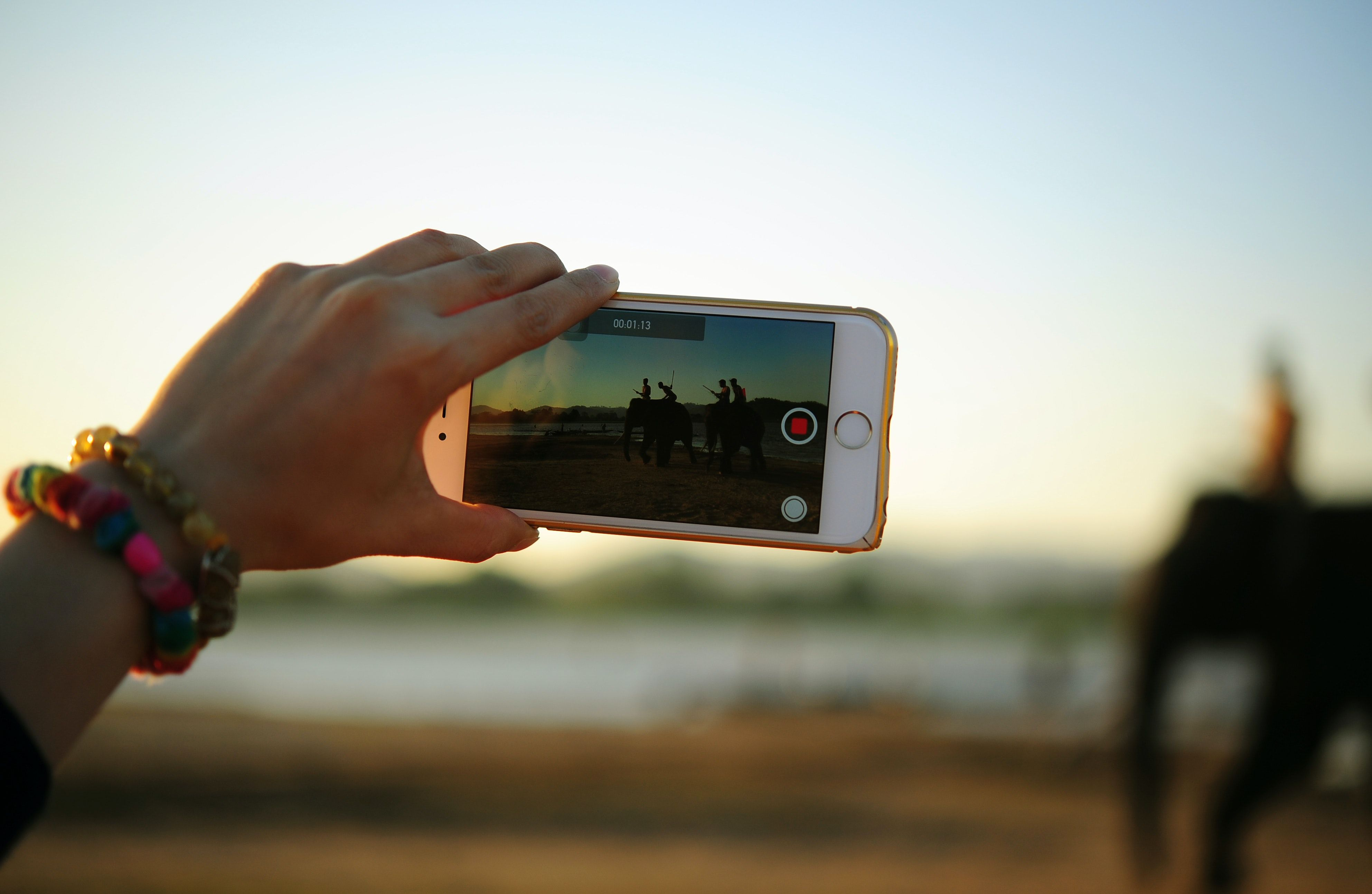 Person holding up a mobile phone to take a photo