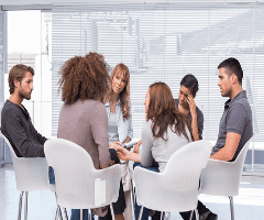 This is a picture of people sitting on chair in a circle