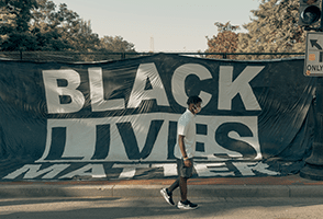 This is a picture of Black Lives Matter flag with a black person walking in front of it