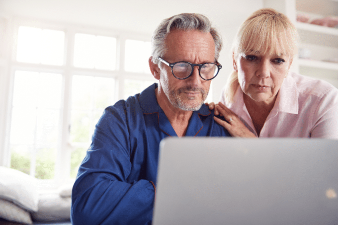 This a picture of two adults on a laptop