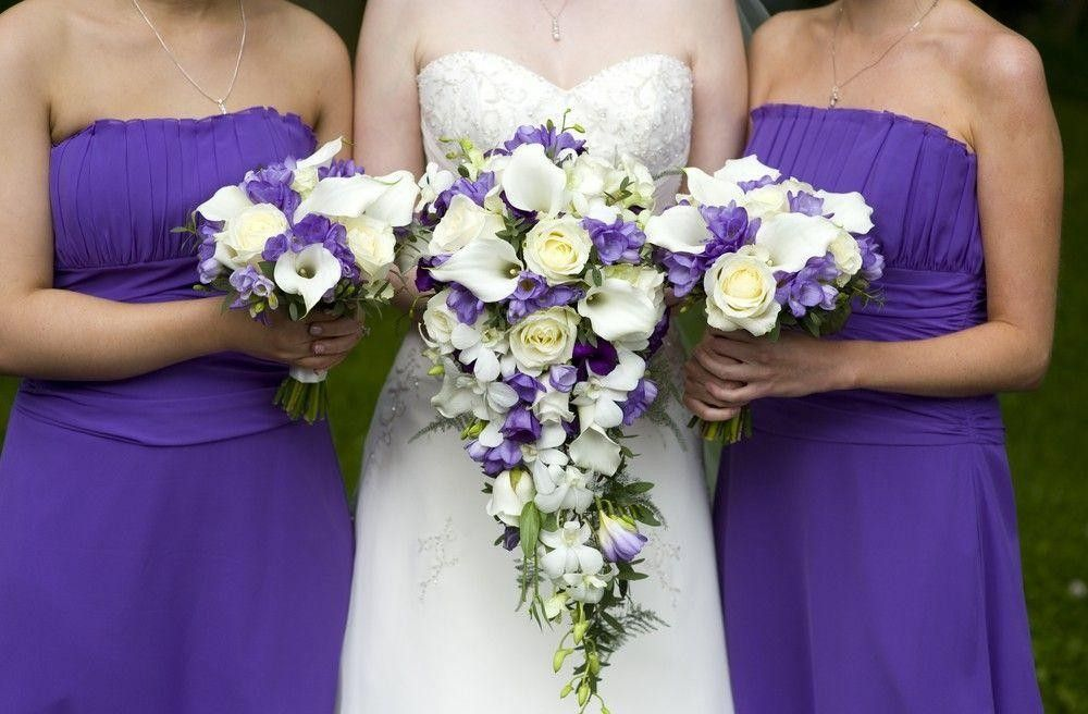 Bride with her 2 bridesmaid with a large bouquet arrangement