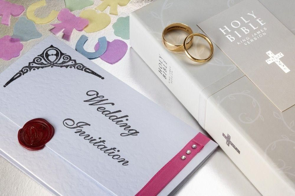 Invitation card with a bible and rings on a table