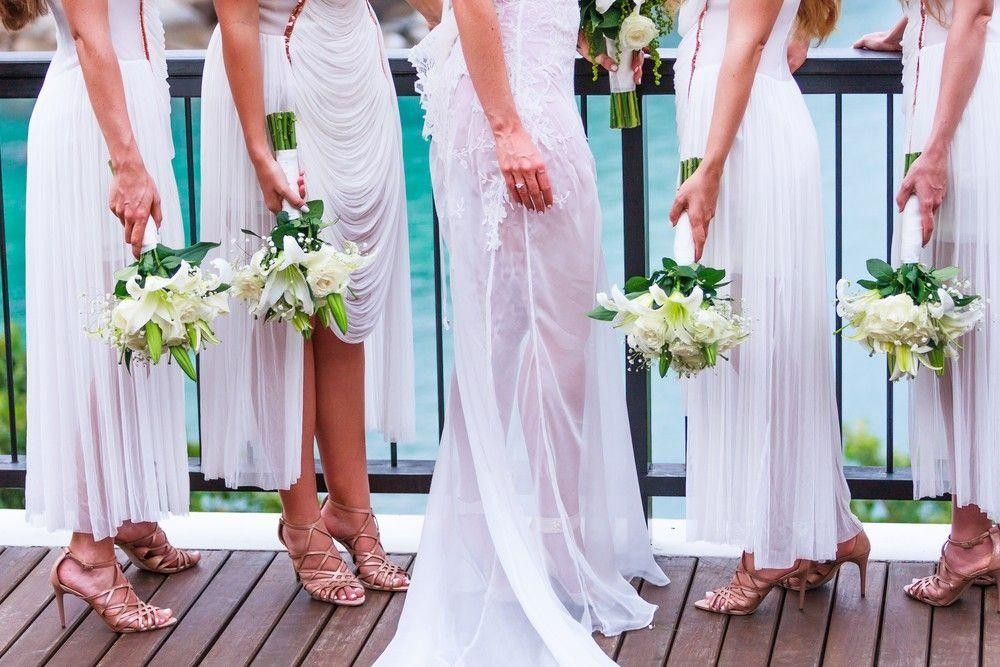 Bridesmaids in white dresses holding a bouquet