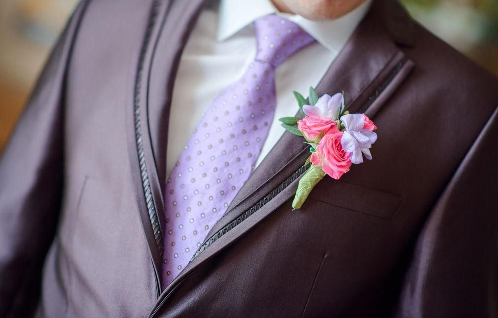Groom in an elegant suit with colored flowers