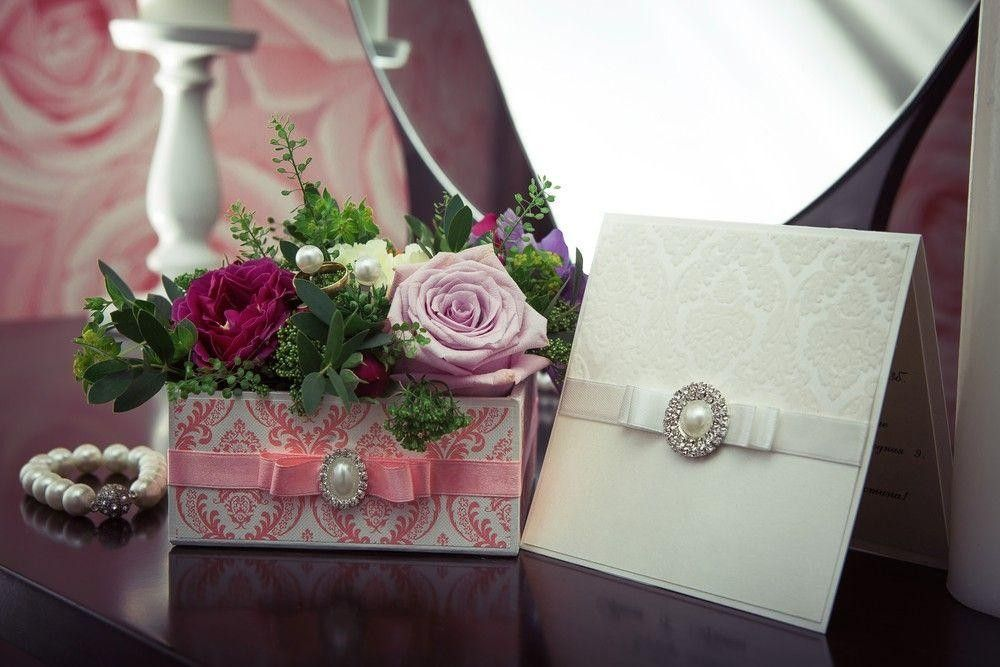 Invitation card on a table with a box of flowers