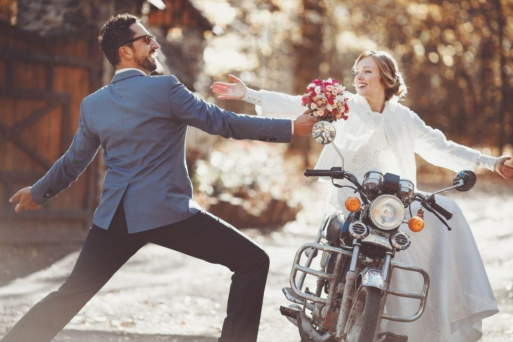 Bride on a motorcycle receiving flowers