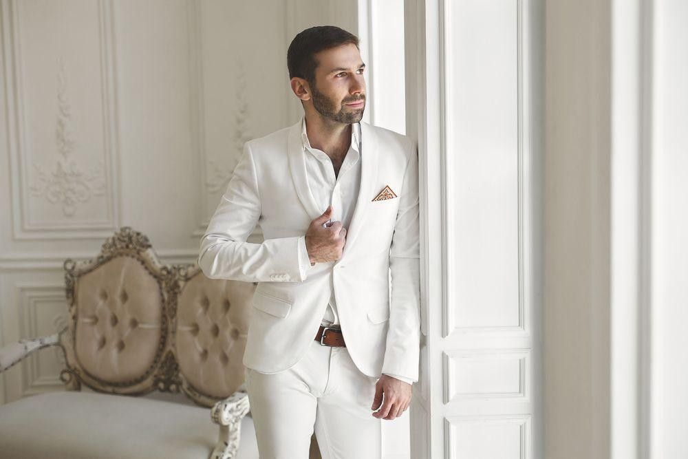 Groom in a white suit by a window