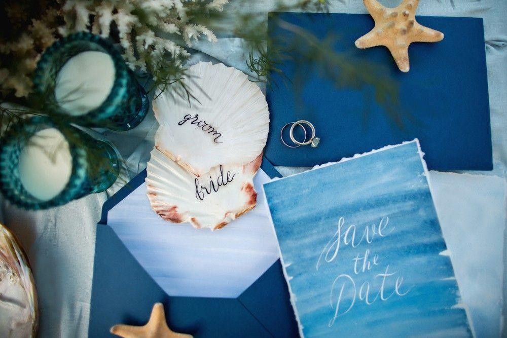 Blue invitation card with a ring and shell on a table