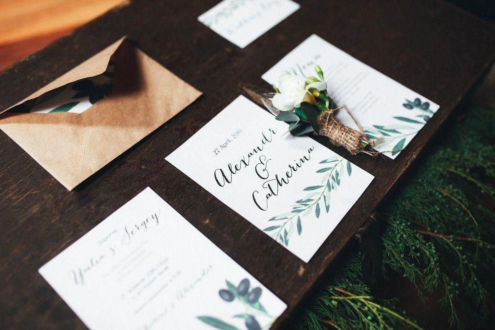 Invitation cards on a table with a flower