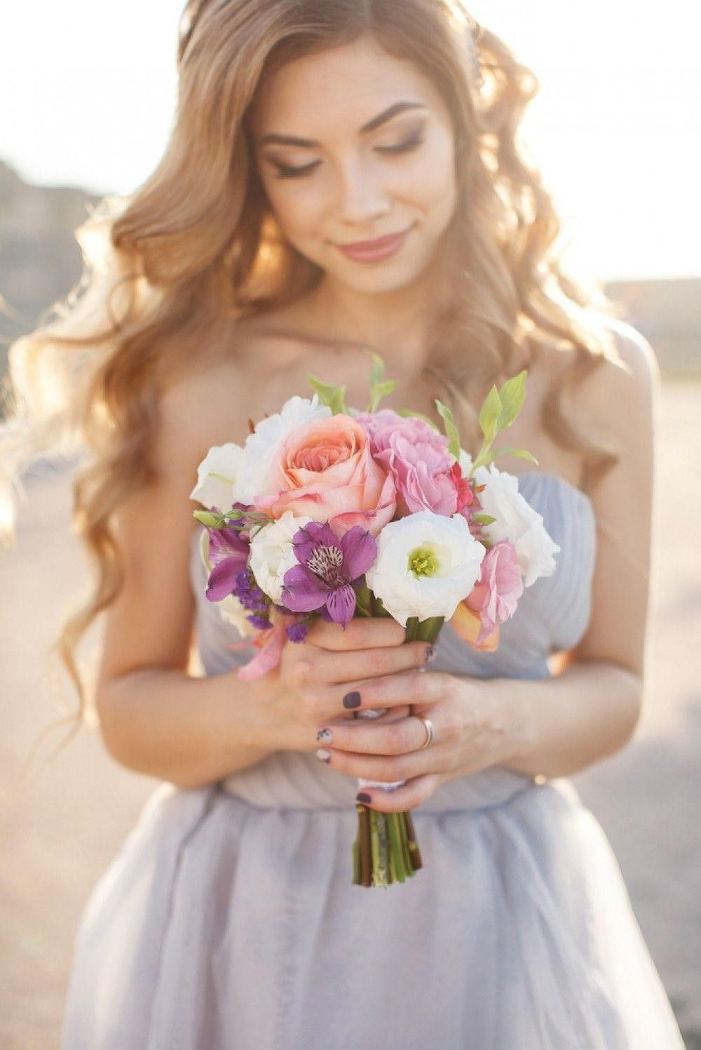 Bride in a grey dress holding a bouquet