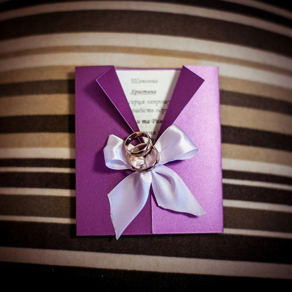 Purple invitation card on a pillow