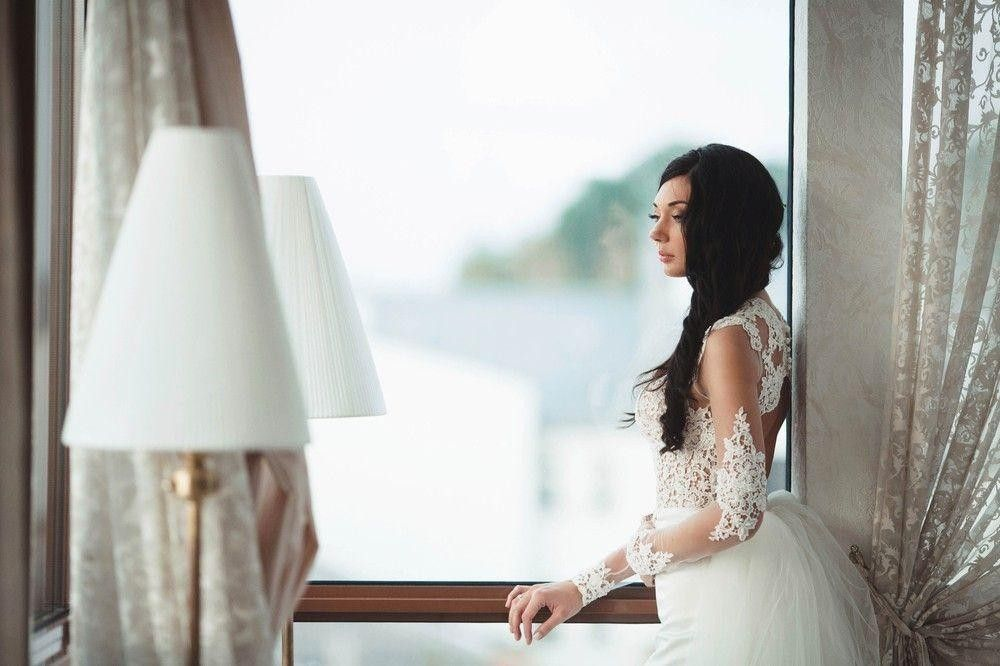 Bride in a white dress by a window