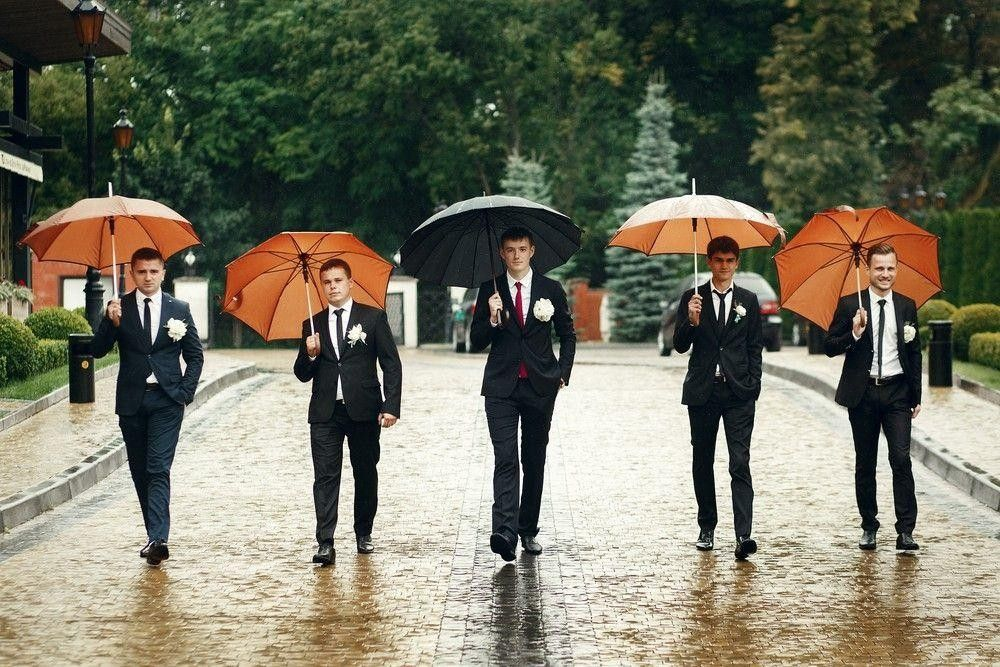 Bestman in the rain with umbrellas