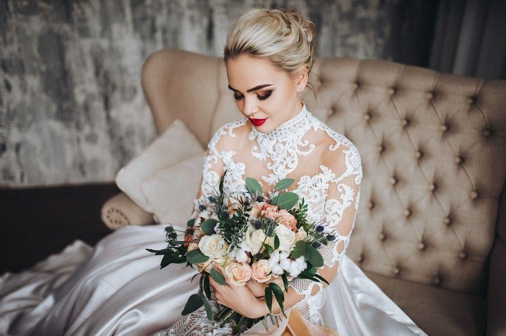 Bride in a white dress sitting with a bouquet