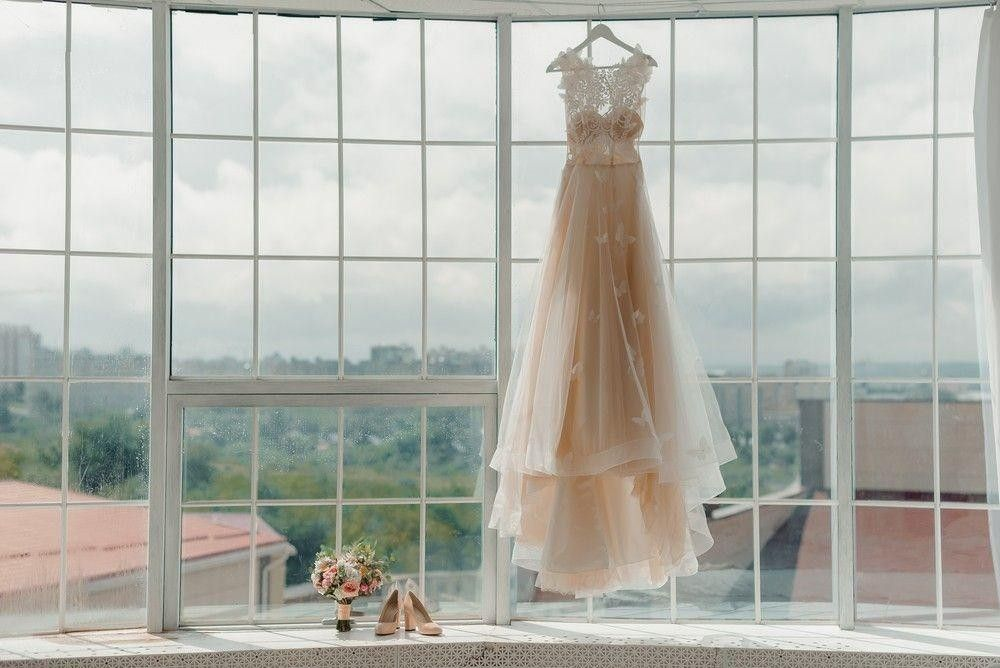 White wedding dress hang in front of a window