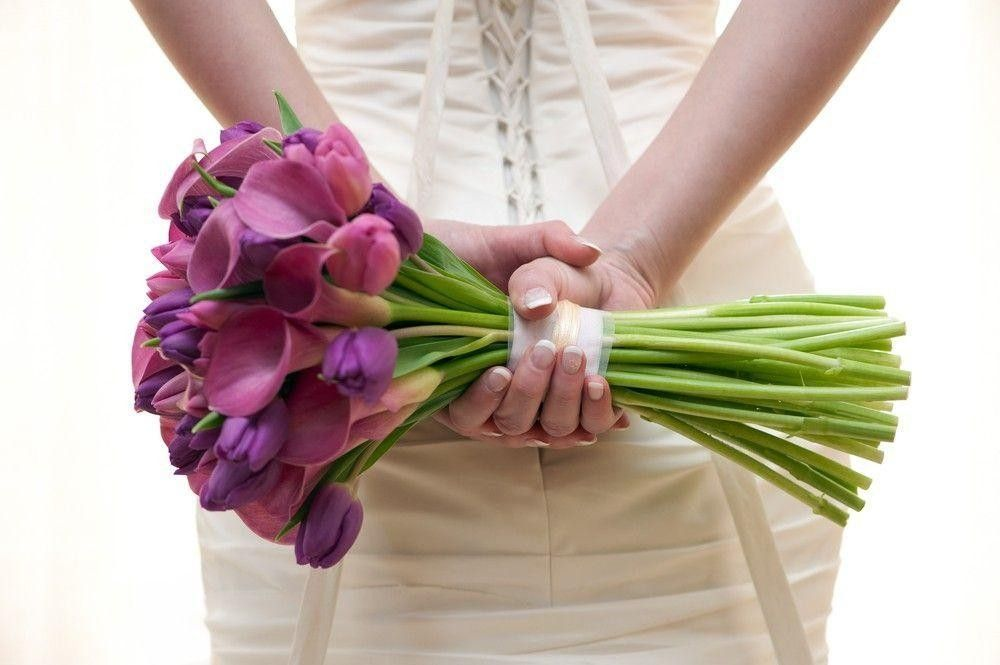Bride holding a fuchsia bouquet on her back
